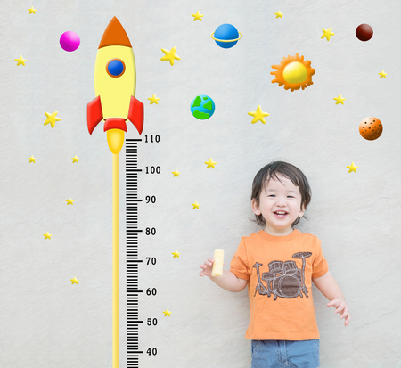 Closeup happy asian kid stand for measure height with cute cartoon at the marble stone wall textured background in growth of kid concept