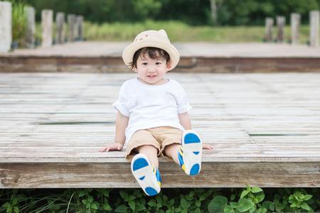 公園バック グラウンドで木製の経路で笑顔顔シッとクローズ アップ ハッピー アジア子供