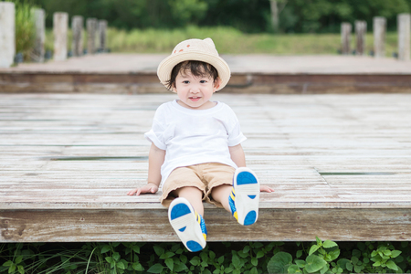 Closeup happy asian kid with smile face sit at wood pathway in the park background Standard-Bild