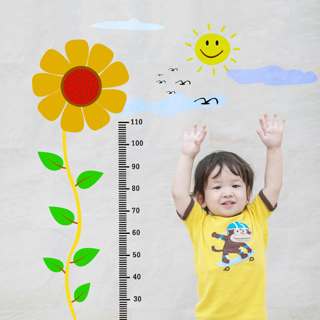 Closeup asian kid stand for measure height with cute cartoon sunflower at the marble stone wall textured background