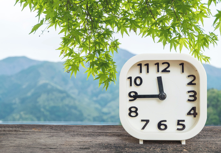 Closeup white clock show a quarter to twelve oclock or 11:45 a.m. on wood desk and blurred green leaves and mountain view background