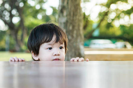Closeup asian kid comes out from the table. in the garden background