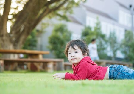 Closeup asian kid lied on grass floor in the garden background with sun light
