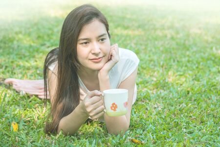 Woman lying on grass field with a cup of coffee in the park Standard-Bild