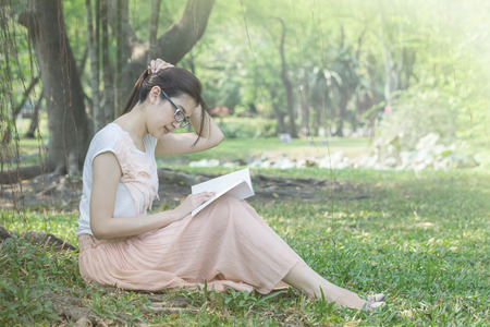 Woman sitting on grass field in the public garden for reading in the morning
