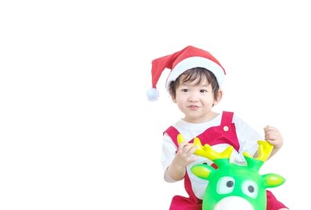 Closeup happy asian kid in santa costume riding reindeer toy isolated on white background in christmas concept