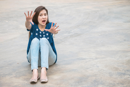 Asian woman with fear emotion on blurred concrete floor texture background