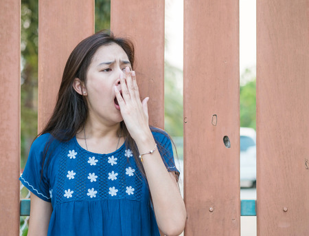 Sleepy asian woman with yawn motion on blurred wooden fence background Stock Photo
