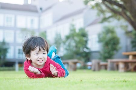Closeup happy asian kid lied on grass floor in the garden background with cute motion Standard-Bild