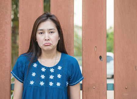 Asian woman with sad face emotion on blurred wooden fence background Stock Photo