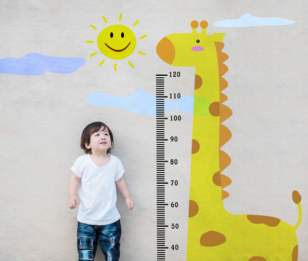 Closeup asian kid stand for measure height and look at cute giraffe cartoon at the marble stone wall textured background Stock fotó