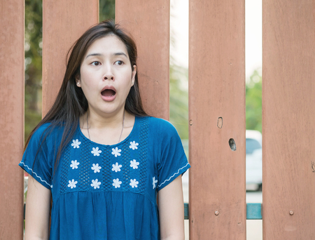 Asian woman with scared face emotion on blurred wooden fence background