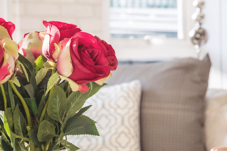 Closeup fake red rose flowers on blurred room view background Stock Photo