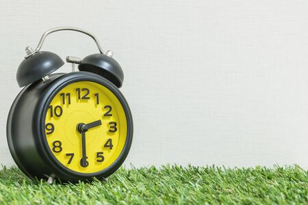 Closeup beautiful alarm clock show the time on half past two oclock or 2:30 p.m. on green artificial grass floor and cream wallpaper in room textured background with copy space