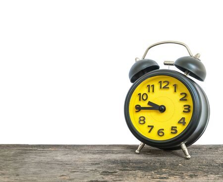 Closeup alarm clock show the time in a quarter to ten oclock or 9:45 a.m. on old brown wood desk isolated on white background with copy space
