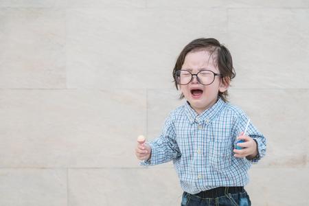 Closeup triste niño asiático llorar porque quiere algo en la pared de piedra de mármol con textura de fondo con espacio de copia