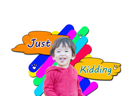 Closeup cute asian kid in cheeky motion with just kidding word in text box isolated on white background Reklamní fotografie