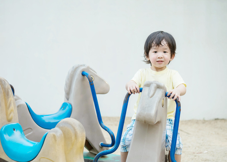 Closeup happy kid with smile face play carousel toy in the playground background Foto de archivo