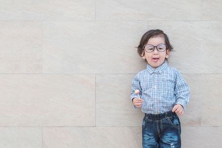 Closeup happy asian kid with eyeglasses enjoy with candy in his hand on marble stone wall textured background with copy space