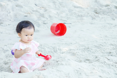 Closeup cute girl make a warped face when sand enter her mouth on beach textured background with copy space