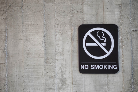 Closeup prohibition signs with no smoking word on old cement wall textued background with copy space