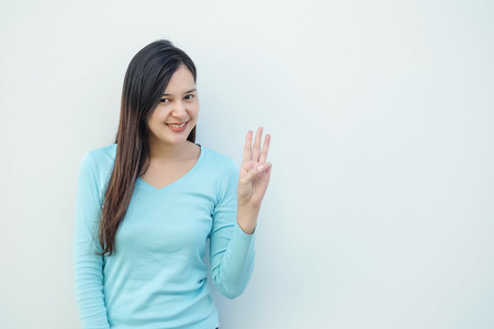 Closeup asian woman holds up three finger motion with smile face on white cement wall background with copy space