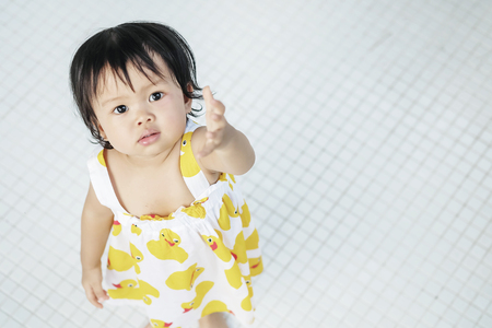 Closeup little girl look like she want something on white tiled floor textured background with copy space Standard-Bild - 118716746