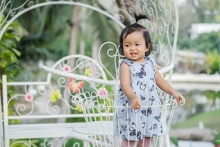 Closeup little girl stand on steel bicycle basket for decorate in the garden background with smile face Standard-Bild - 118716750
