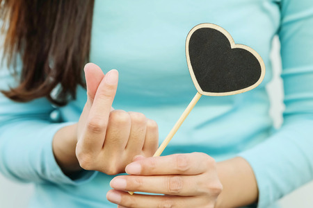 Closeup wooden black board in heart shape with finger of woman in mini heart symbol Standard-Bild - 120314489