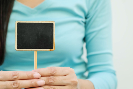Closeup wooden black board in square text box shape on blurred body of woman textured background Standard-Bild - 120314492