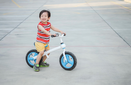 Closeup cute kid with smile face ride a bicycle on cement floor at the car park textured background with copy space Imagens
