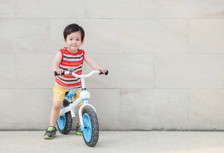 Closeup cute asian kid ride a bicycle on stone marble wall and floor textured background with copy space Standard-Bild - 120314500
