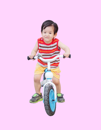 Closeup cute asian kid ride a bicycle isolated on pink background Standard-Bild - 122498145