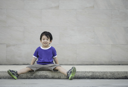 Closeup happy asian kid with smile face sit at pathway on marble stone wall textured background with copy space Standard-Bild - 122498154