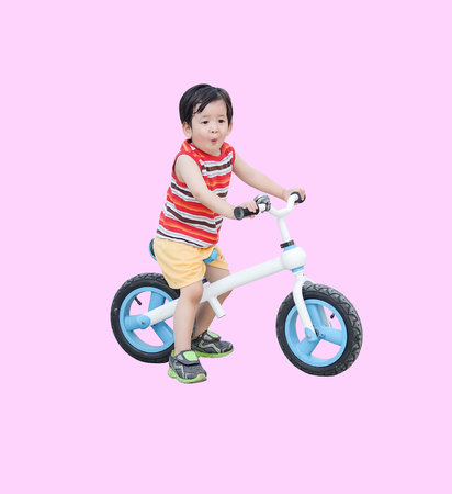 Closeup cute asian kid ride a bicycle in excited mood isolated on pink background