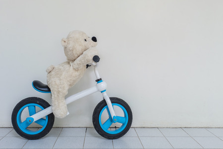 Closeup bear doll ride a bicycle for kid on white cement wall textured background with copy space Standard-Bild - 122572836