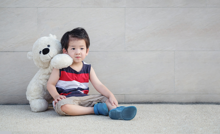 Closeup asian kid with bear doll sit at pathway on marble stone wall textured background with copy space Standard-Bild - 122572833
