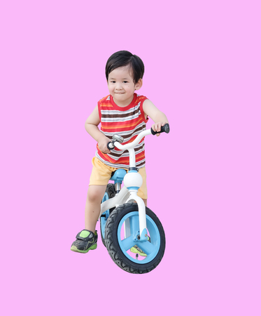 Closeup cute asian kid ride a bicycle isolated on pink background