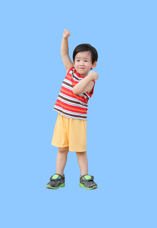 Closeup happy kid with funny motion isolated on blue background Imagens