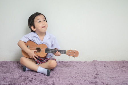 Closeup a little kid in student uniform play ukulele on carpet with copy space