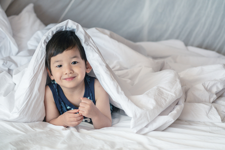 Closeup asian kid on bed under blanket with smile face in the morning