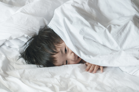 Closeup asian kid on bed with smile face in the morning Foto de archivo