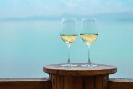 Closeup two white wine glass on the table at the terrace on sea view background Stock fotó