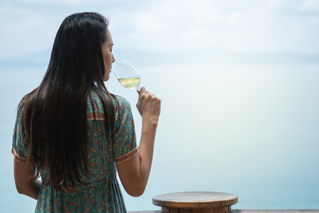 closeup women drink white wine with a glass of wine at the terrace on sea view background in the evening Stock fotó