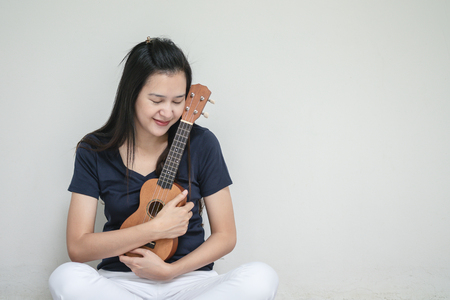 Closeup asian woman with ukulele on white cement wall texture background