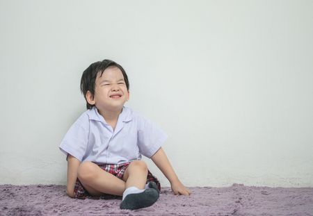 Closeup a little kid in student uniform with smile face sit on carpet and white wall textured background with copy space