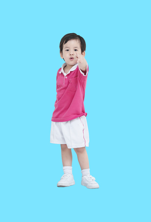 Closeup asian boy in sport wear uniform pointing finger to someone isolated on blue background