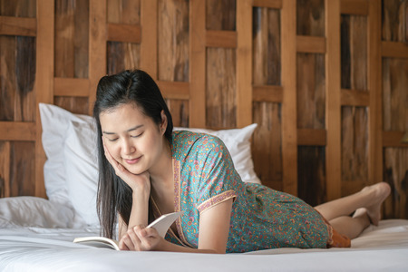 Closeup woman reading a book on bed in her bedroom in the morning