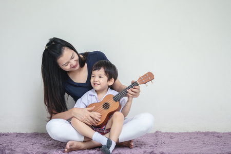 Asian mother teach her son to play ukulele on carpet with copy space