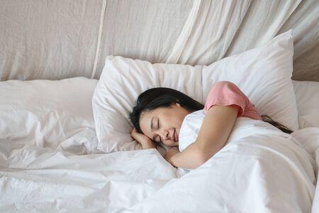 Closeup mujer asiática duerme en la cama debajo de la manta en el fondo del dormitorio por la mañana